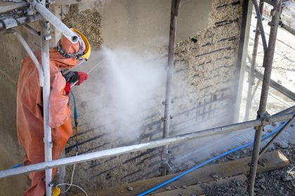 Worker in orange protective suit cleans corrosion damaged concrete bridge pillar with high pressure washer